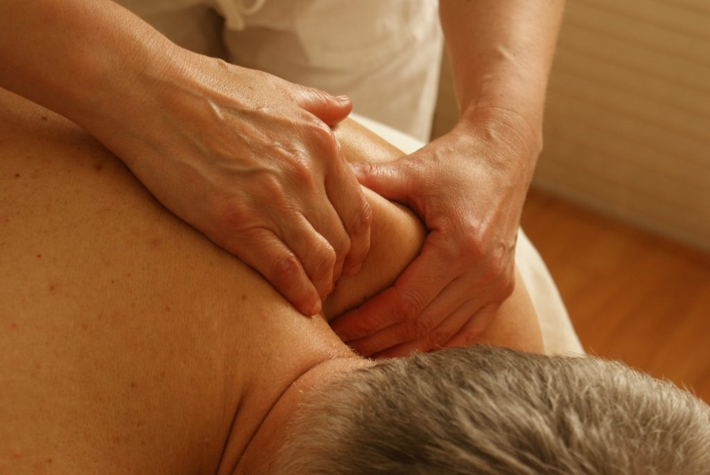 mobile massage therapist massaging guy with grey hair shoulders