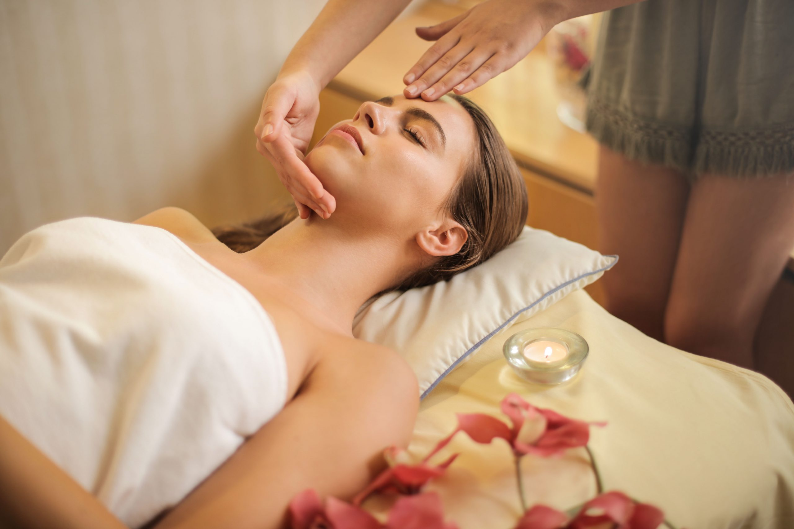 Woman wrapped in white towel lying on bed getting mobile massage in London