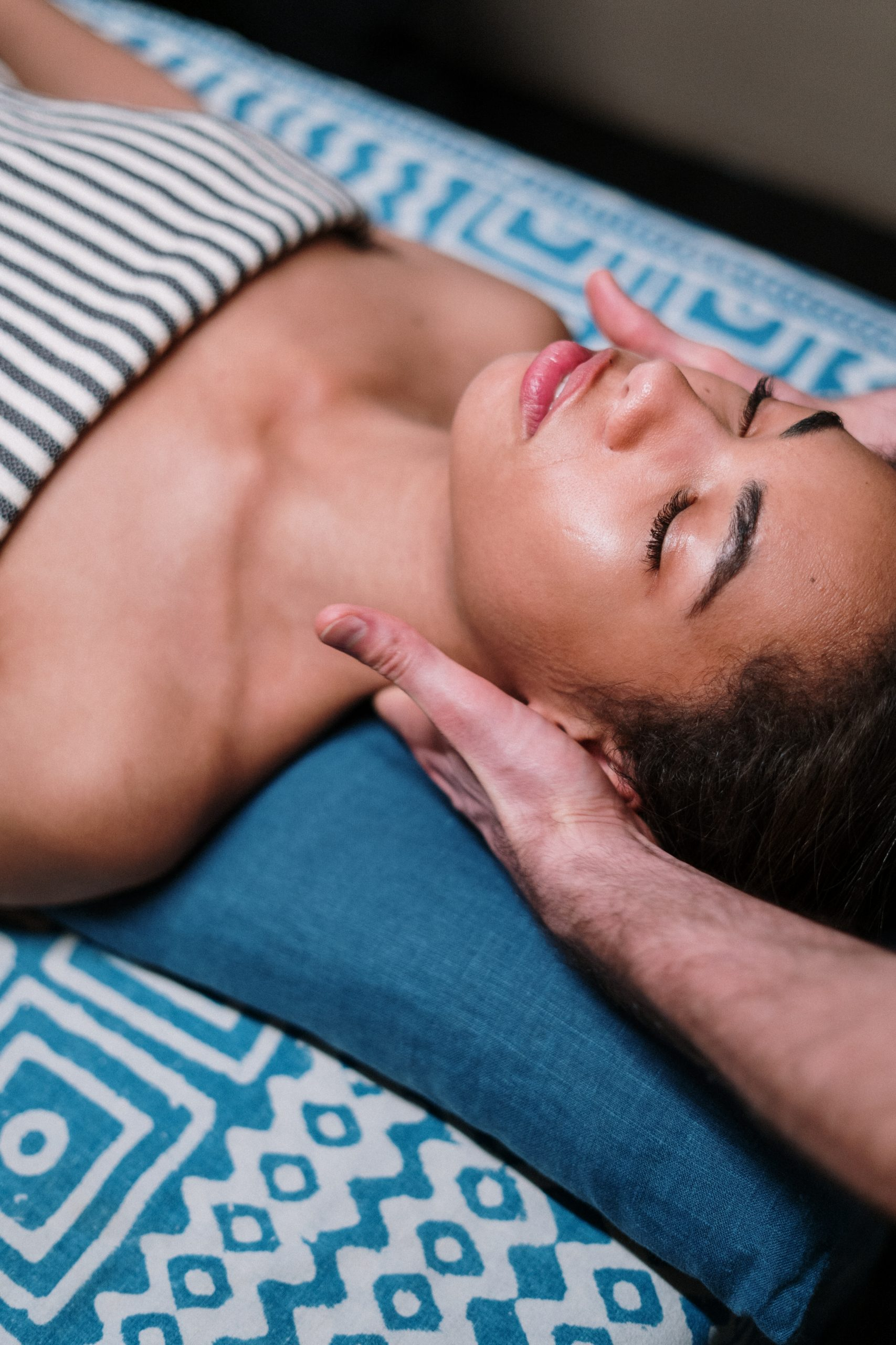 woman laying on blue textile having neck massaged by a massage home service therapist